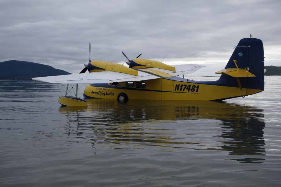 A picture of a yellow and blue Grumman Widgeon on the water